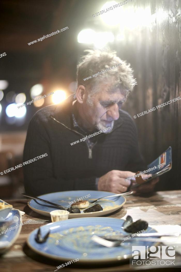 Stock Photo: Friesian senior man checking phone in restaurant after having fish for dinner.