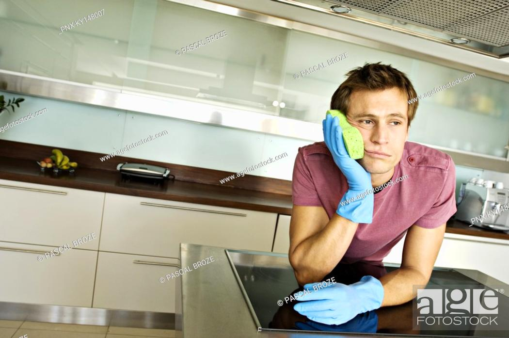Stock Photo: Young man in kitchen, leaning sponge against his cheek.