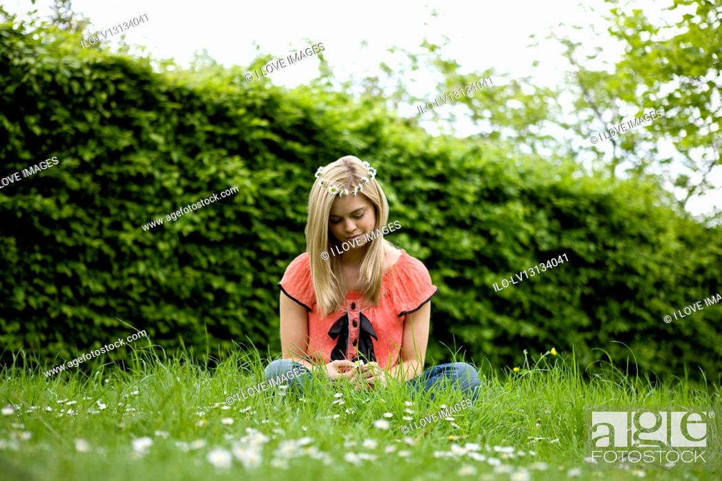 Stock Photo: A young woman sitting on the grass, holding a daisy.