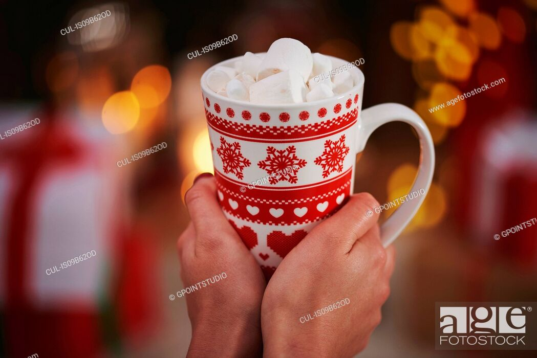 Stock Photo: Woman holding hot chocolate in festive mug.