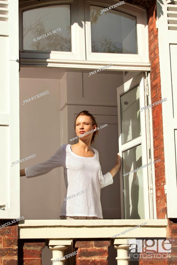 Stock Photo: Young woman opening window.