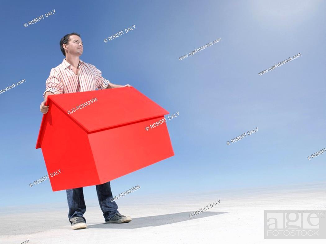 Stock Photo: Man holding small model house in desert.
