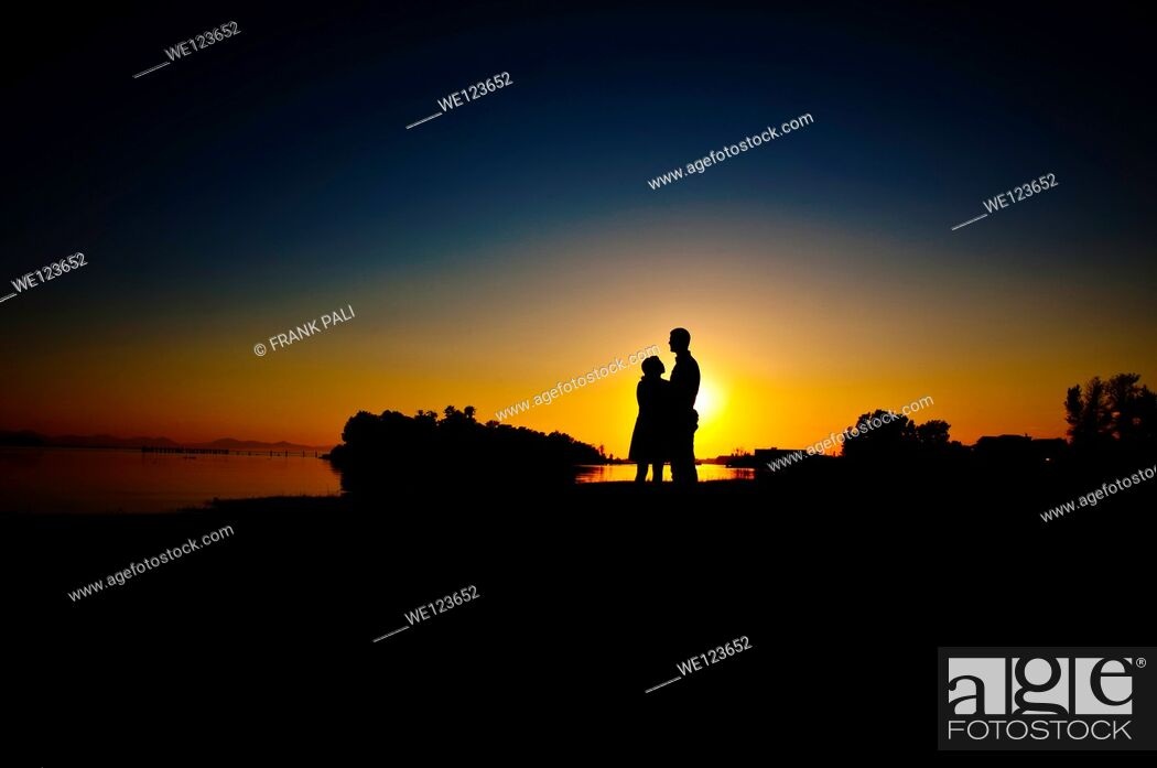 Imagen: Silouette of couple standing by the shore with the sun setting in background of couple standing by the shore with the sun setting in background.