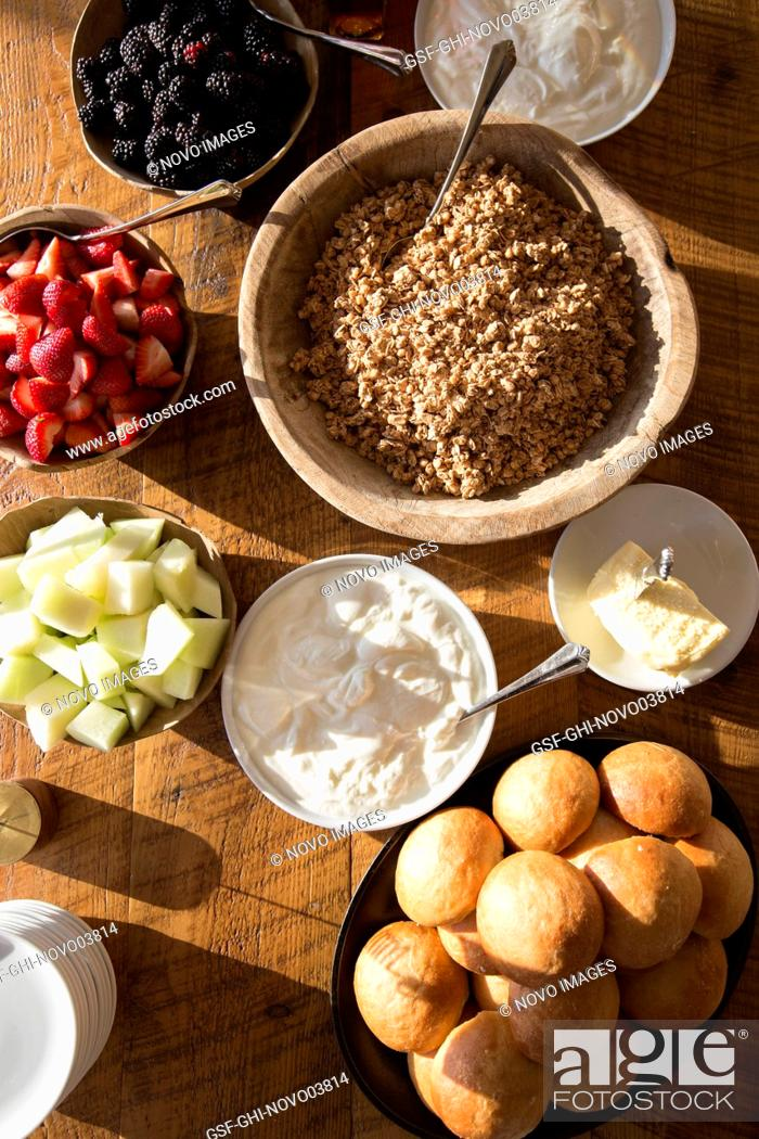 Imagen: High Angle View of Bowls of Granola, Yogurt and Fresh Fruit on Wood Table.