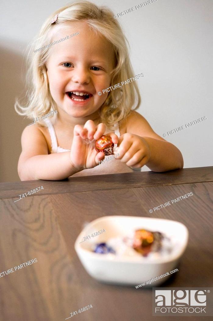 Stock Photo: Little girl peeling a bonbon.