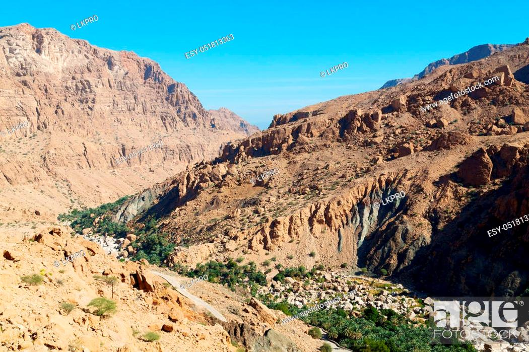 Stock Photo: gorge and canyon the deep cloudy sky in oman the old mountain.