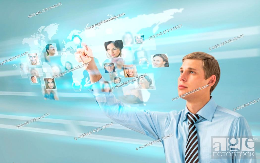 Stock Photo: Young successful man looking at worldmap with profile photos of his colleagues and touching virtual screen. International communication concept.