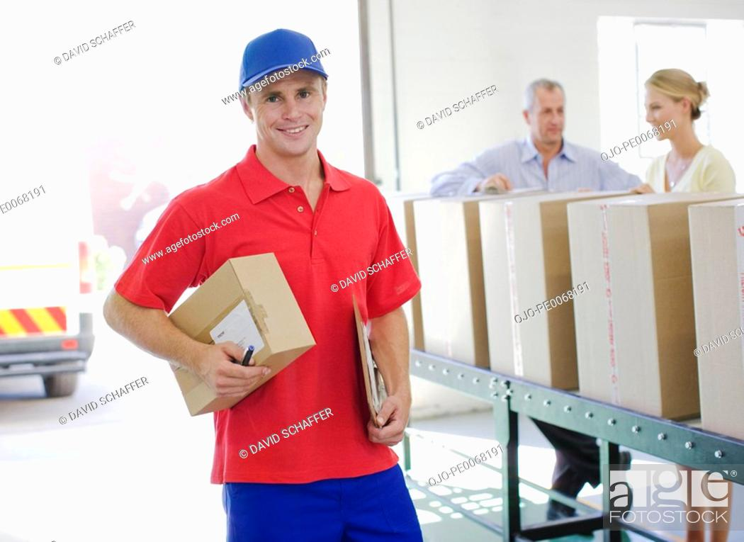 Stock Photo: Delivery man holding cardboard box in warehouse.