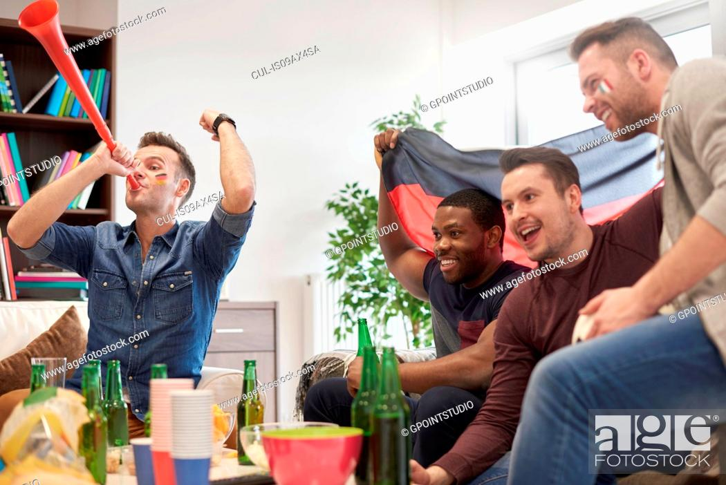 Imagen: Group of men watching sporting event on television holding German flag celebrating.