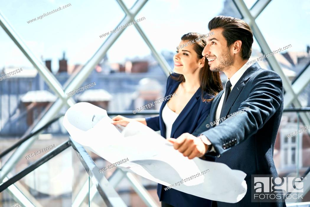 Stock Photo: Smiling businesswoman and businessman holding plan in office.