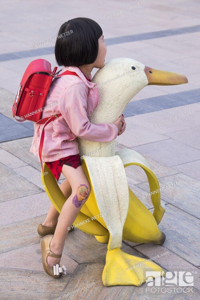 Stock P O Little Girl Posing On A Banana Duck Street Art In Dubai