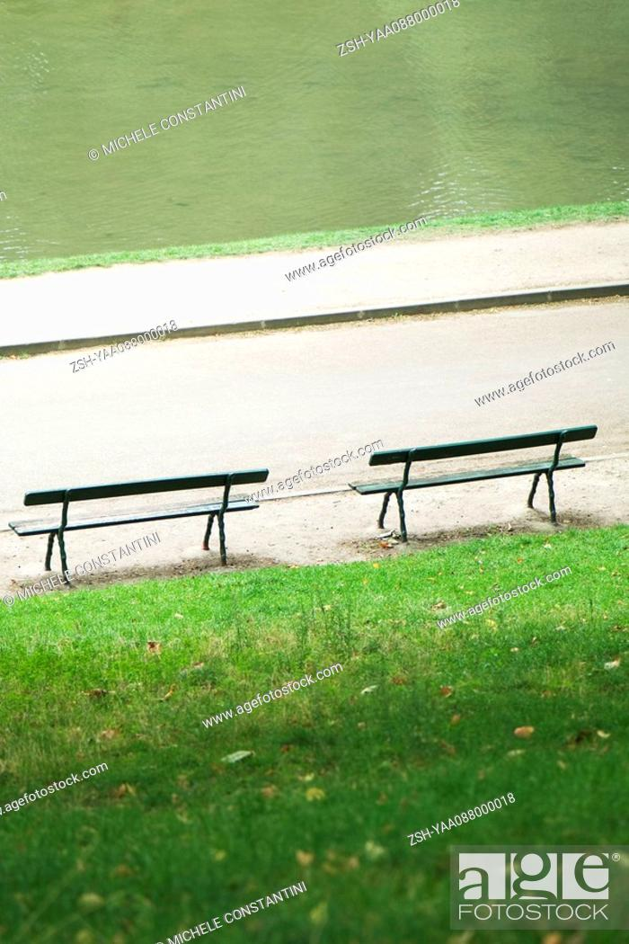 Stock Photo: France, Paris, benches facing water in park.