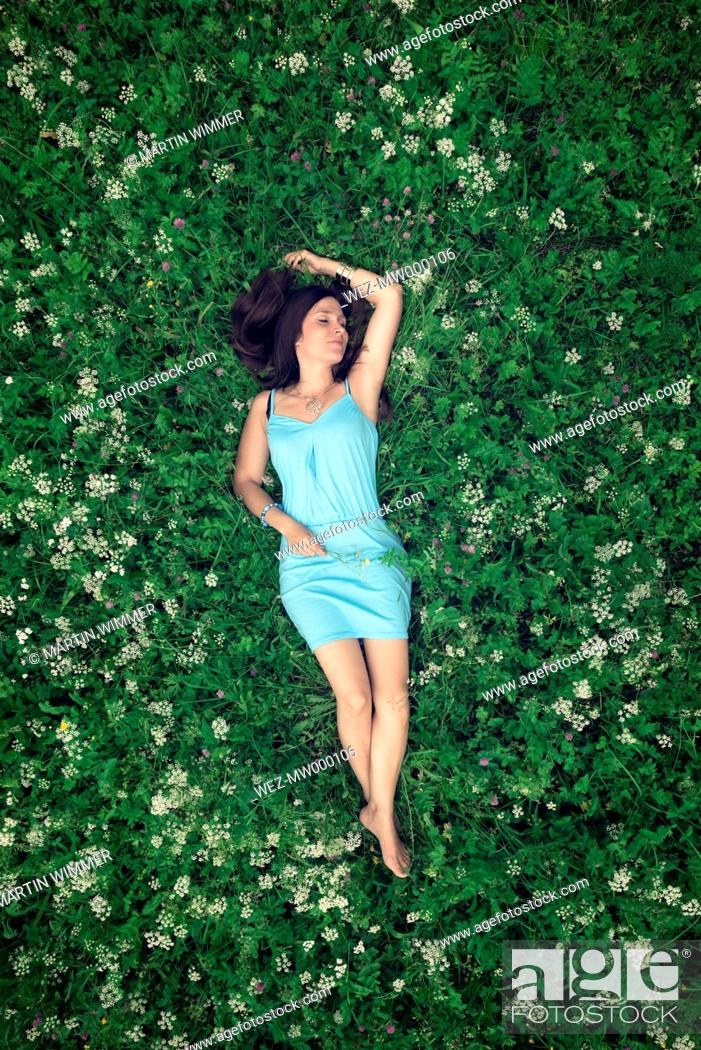 Imagen: A young woman in a blue dress lying on a summer meadow.