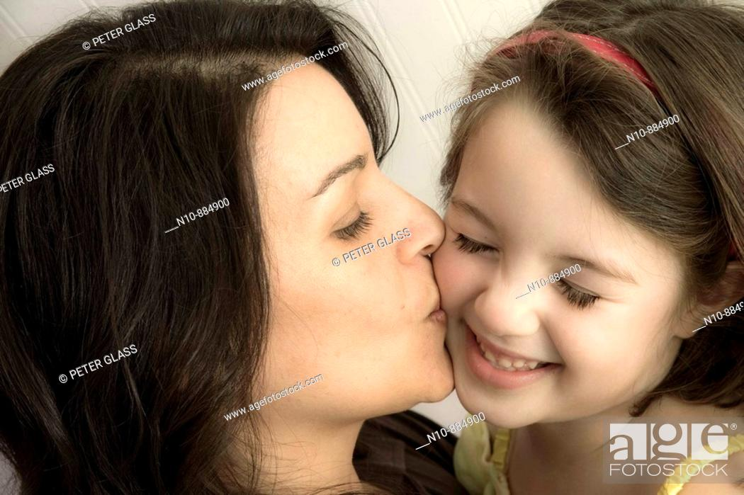 Stock Photo: Mother kissing her young daughter.  Model and Property Released.
