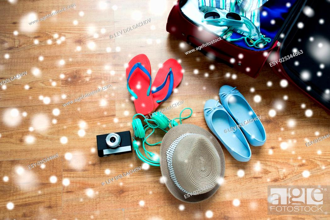 Stock Photo: winter holidays, vacation, tourism and objects concept - travel bag with clothes and stuff over snow.