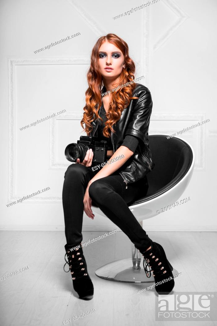 Stock Photo: Trendy red-haired woman posing with camera in a chair.