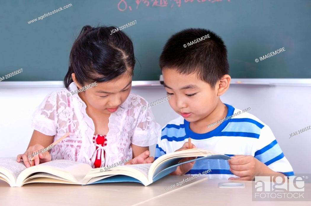 Stock Photo: Child, Two children reading book together and learning.