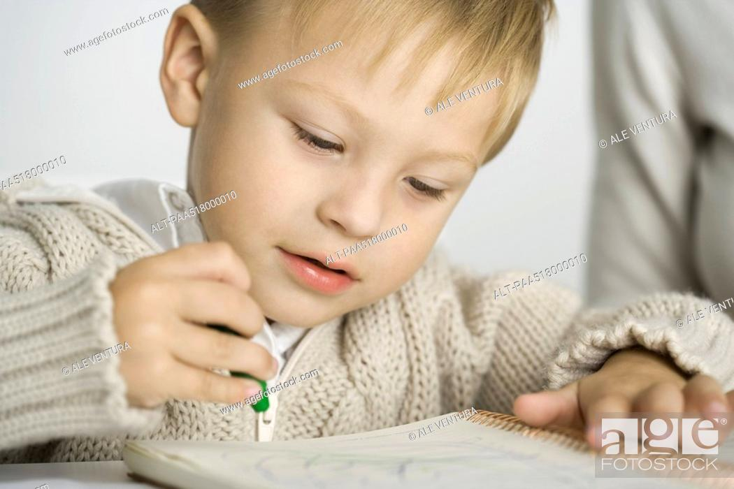 Stock Photo: Little boy coloring with crayon, close-up.