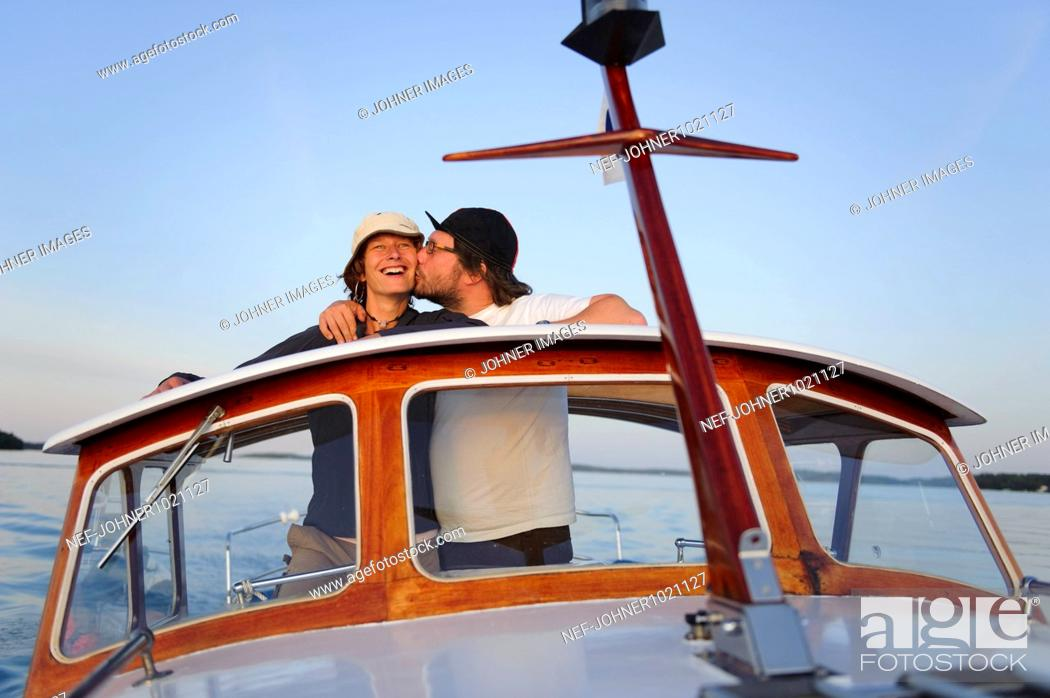 Stock Photo: Man kissing woman on motorboat.