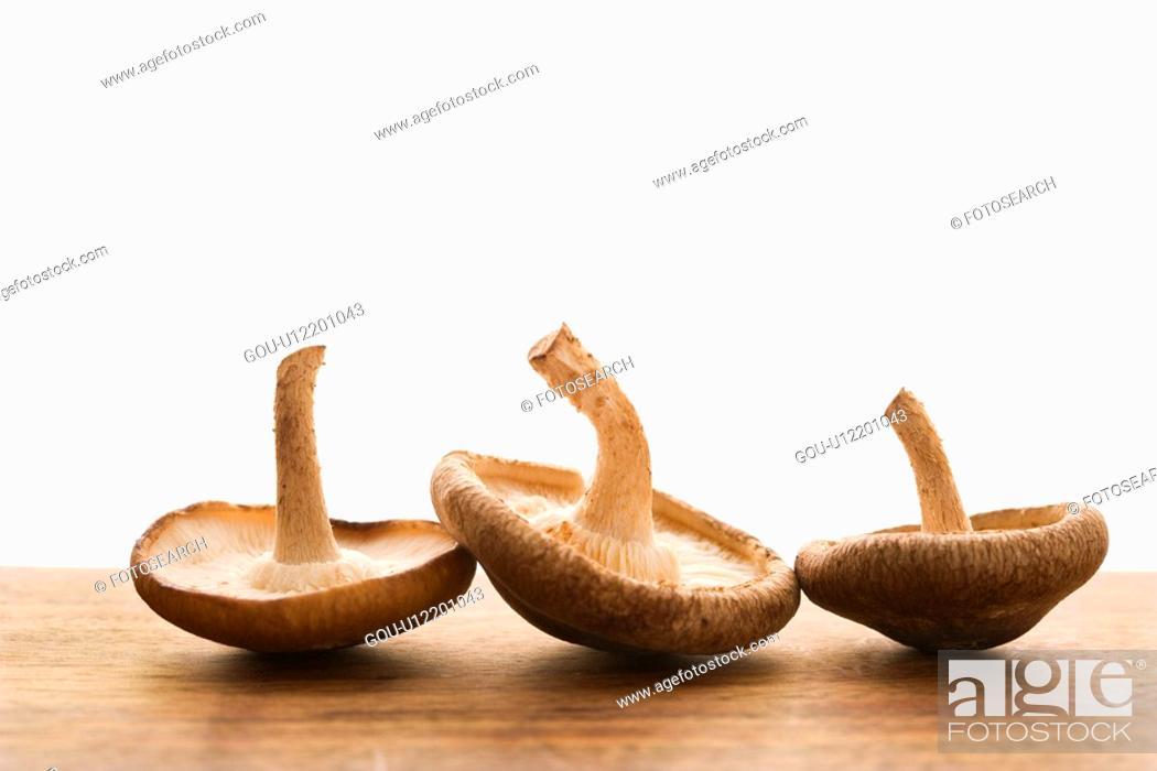 Stock Photo: Three brown mushrooms upside down.