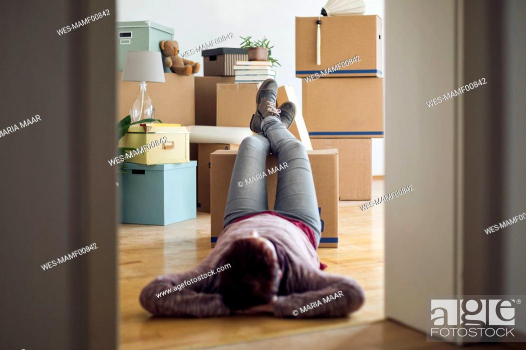 Photo de stock: Woman relaxing surrounded by cardboard boxes in a new home.