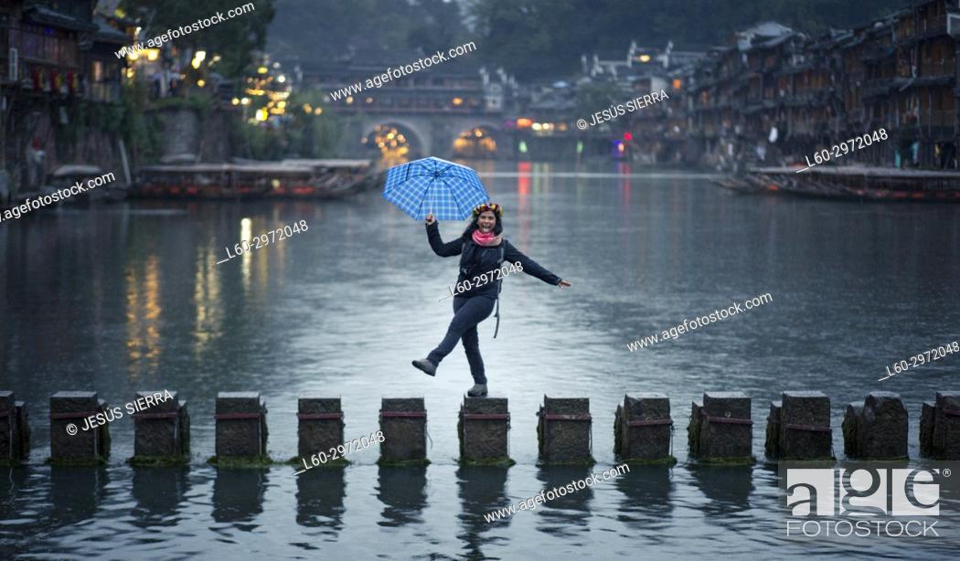 Stock Photo: Happy girl in the ancient town, Fenghuang, Hunan Province, China.