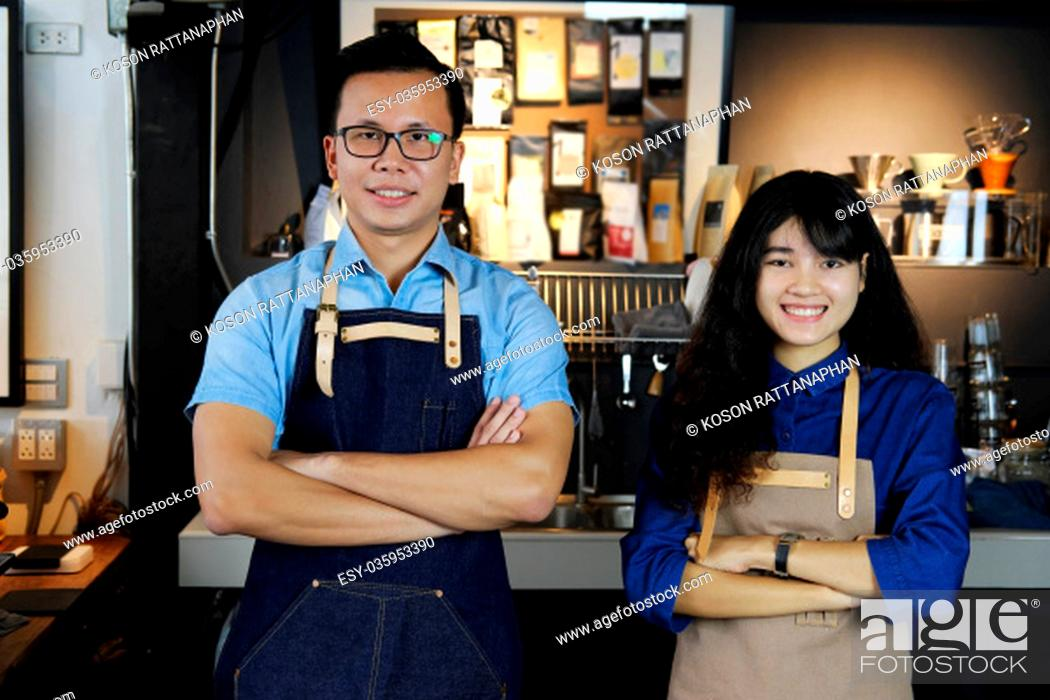 Stock Photo: Portrait of smiling asian barista team with arms crossed at counter in coffee shop. Cafe restaurant service, Small business owner.