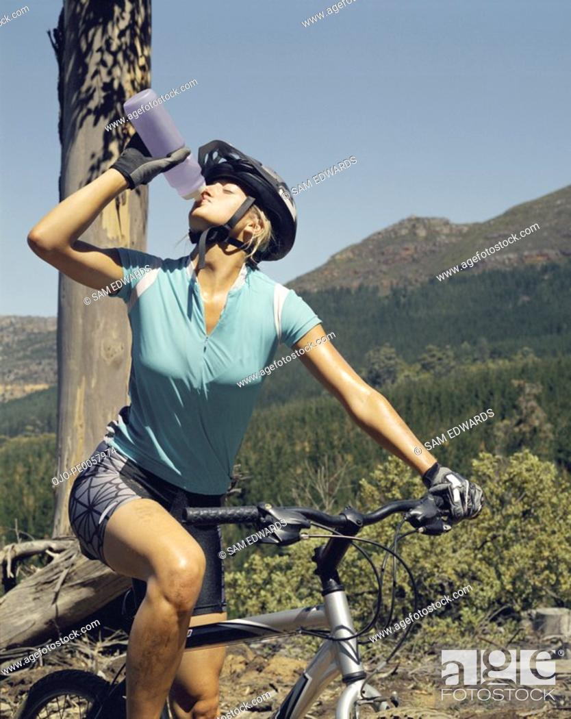 Stock Photo: A woman drinking a bottle of water on her bike.