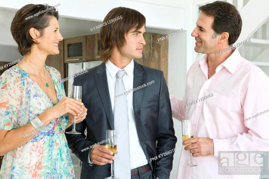 Stock Photo: Man drinking champagne with his parents.