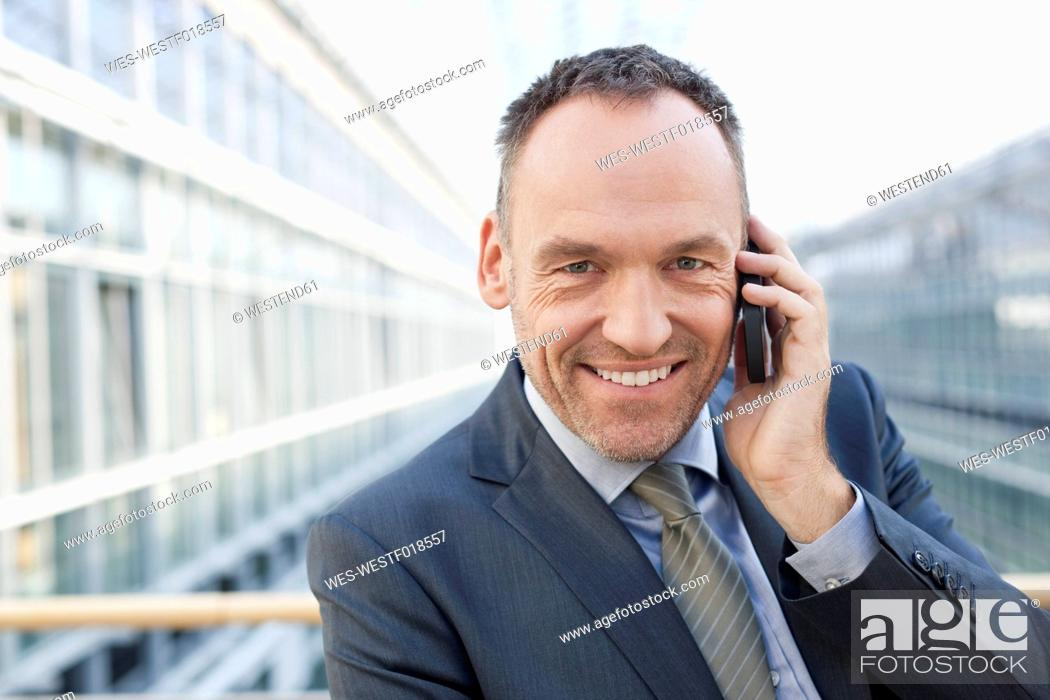 Stock Photo: Germany, Leipzig, Businessman on cell phone, smiling, portrait.
