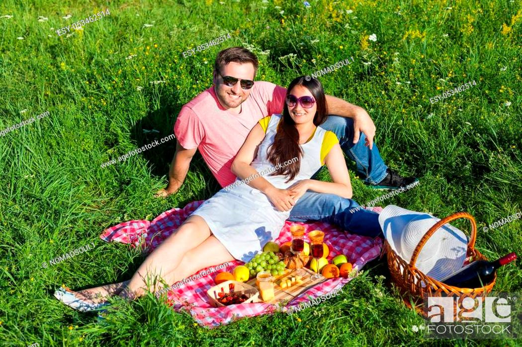 Stock Photo: Young couple having picnic on the meadow.