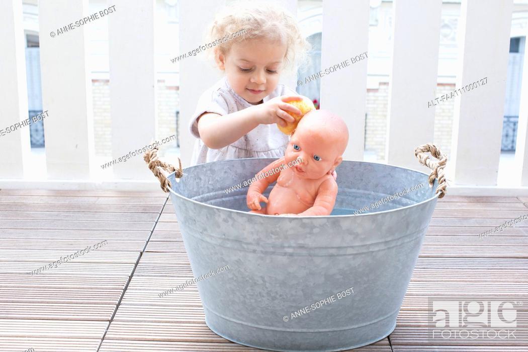 Stock Photo: Little girl bathing baby doll in bucket outdoors.