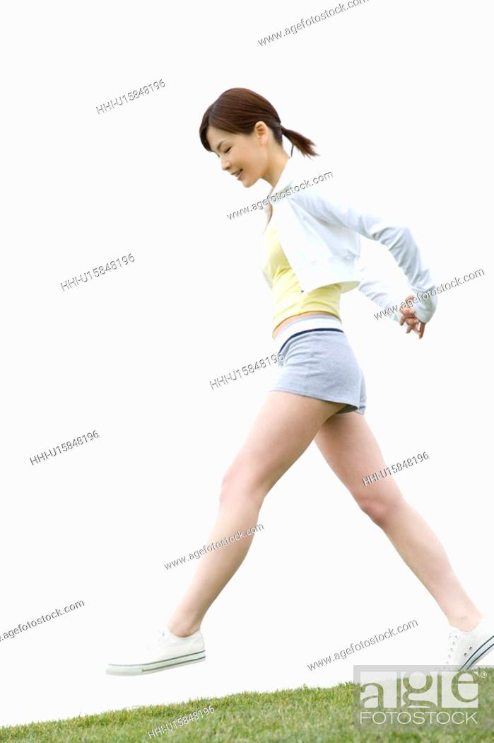 Stock Photo: Young Woman walking on lawn, low angle view.