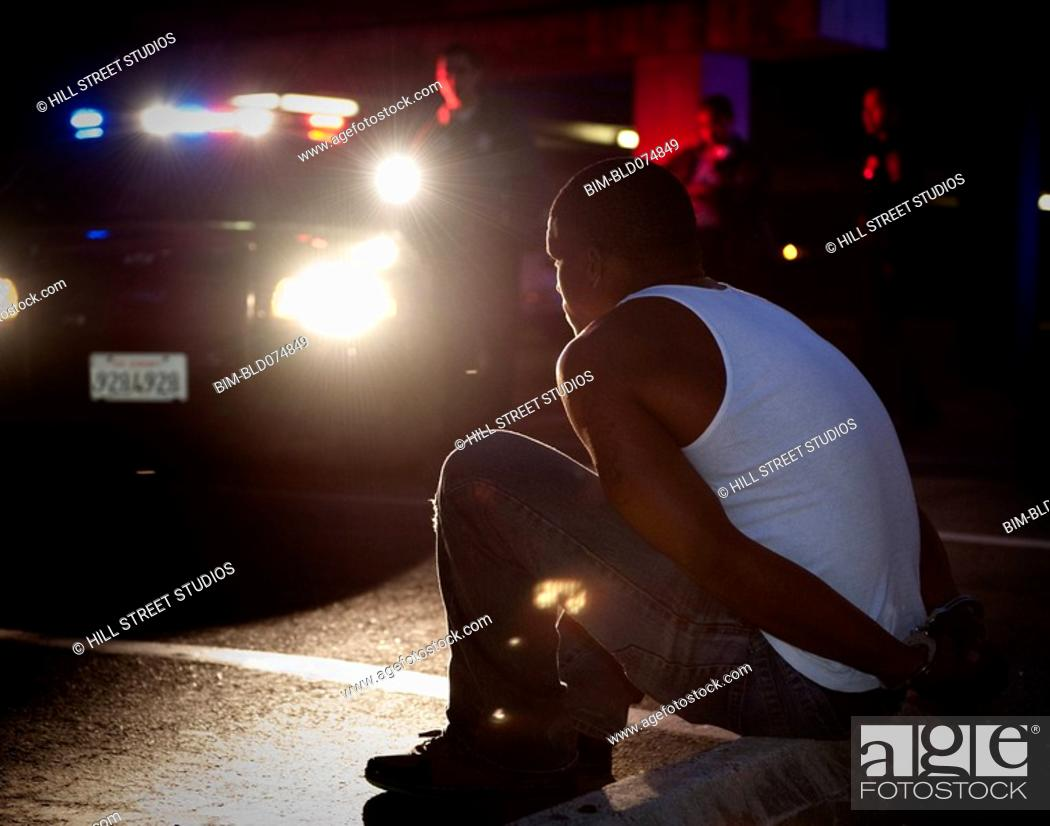Stock Photo: Police shining lights on handcuffed African man sitting on curb.