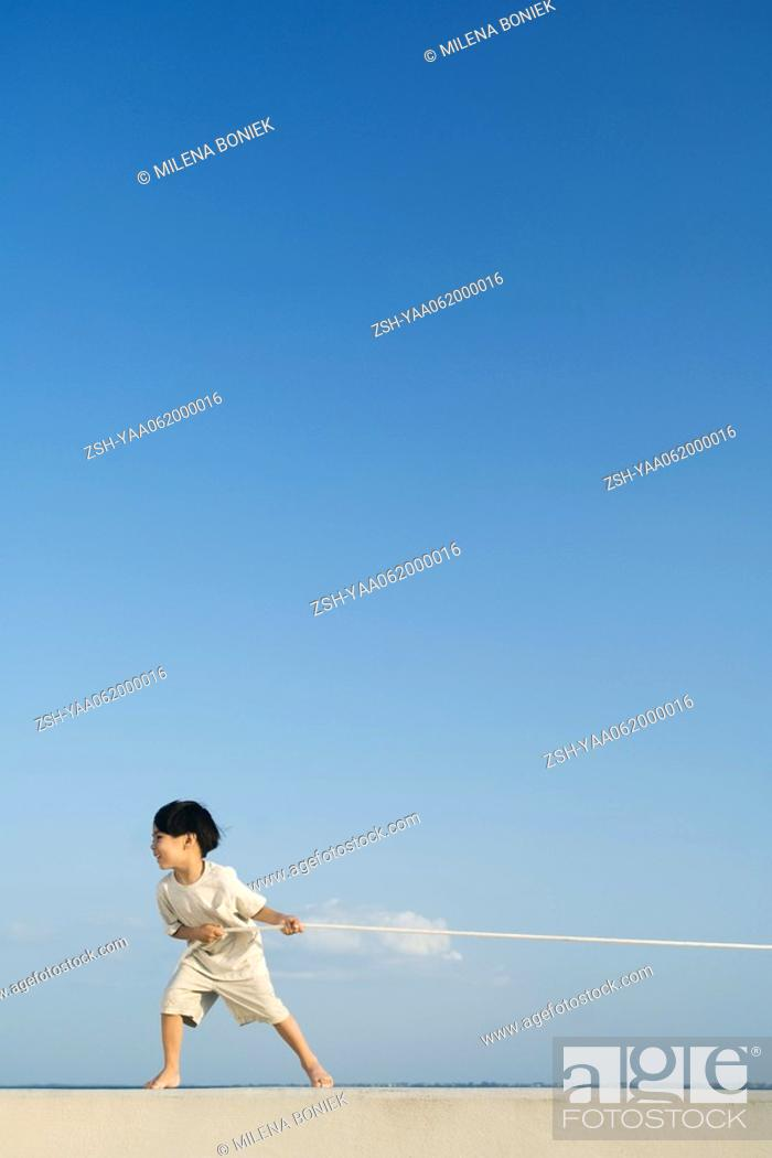 Stock Photo: Little boy playing tug-of-war outdoors, side view.