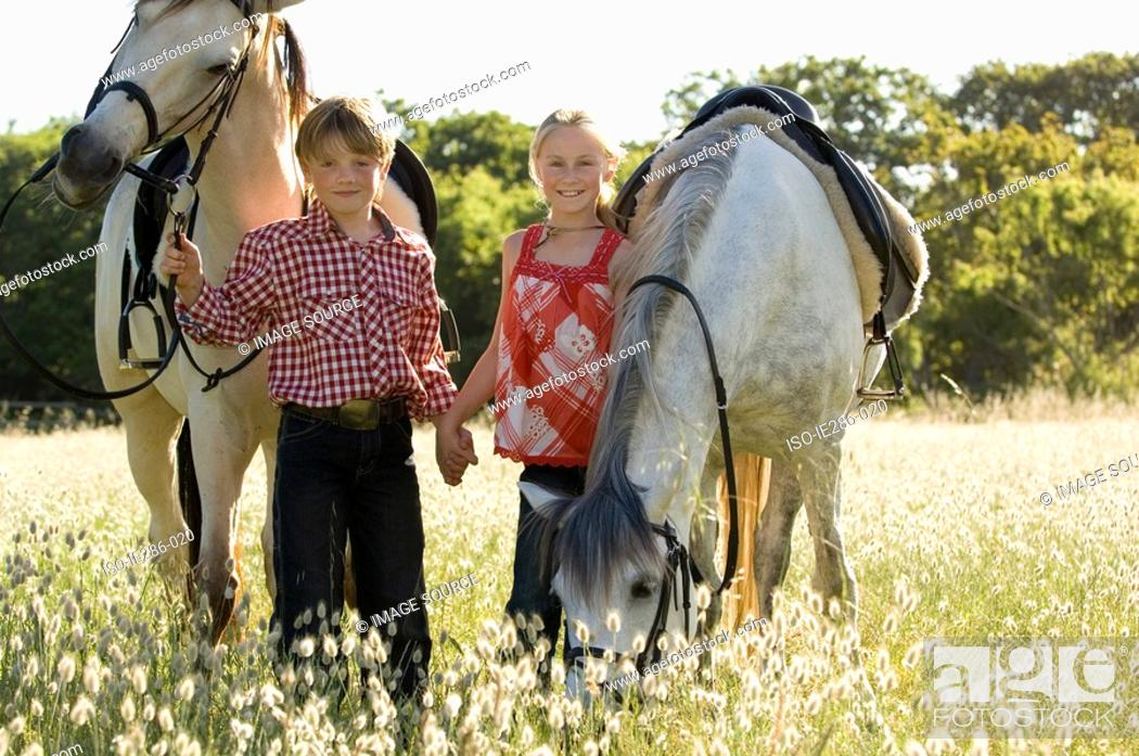Stock Photo: A boy and girl with horses.