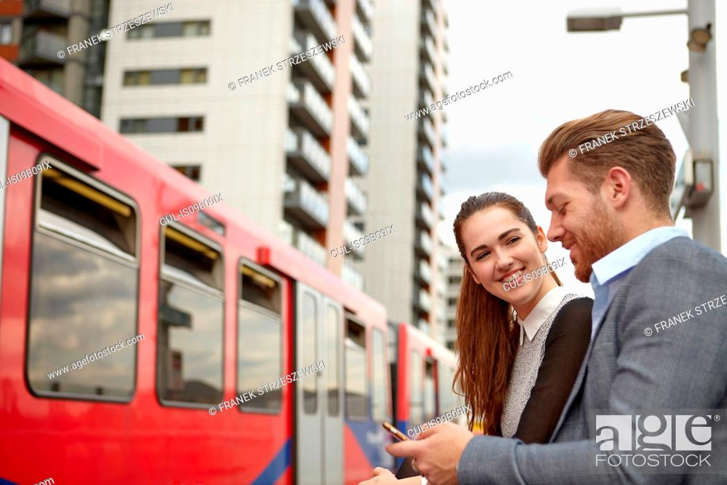 Stock Photo: Businessman and woman reading smartphone texts on railway platform, London, UK.