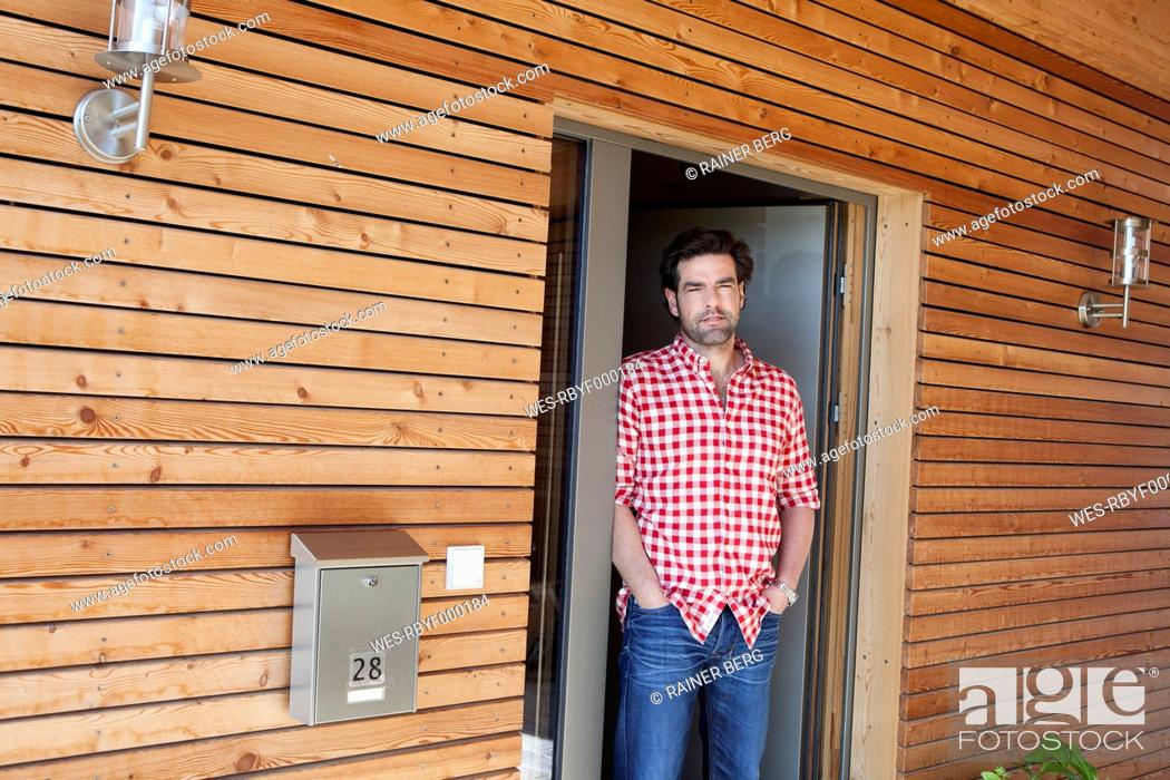 Stock Photo: Germany, Bavaria, Nuremberg, Mature man standing at front door of house.