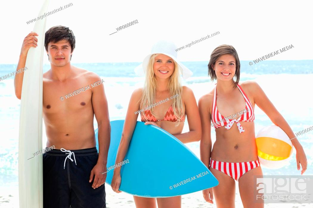 Stock Photo: Man and two women looking forward with surfboards and smiling.