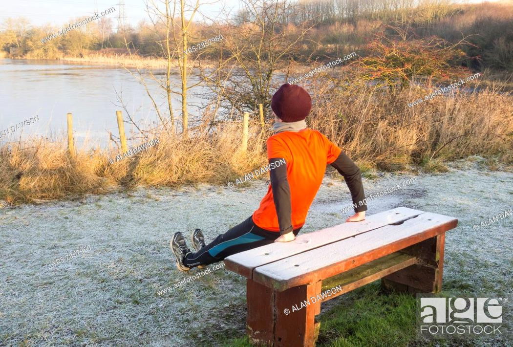 Stock Photo: Billingham, north east England, UK. A mature male jogger warming up on a frost covered bench in Cowpen Woodland Park just after sunrise on a clear and frosty.