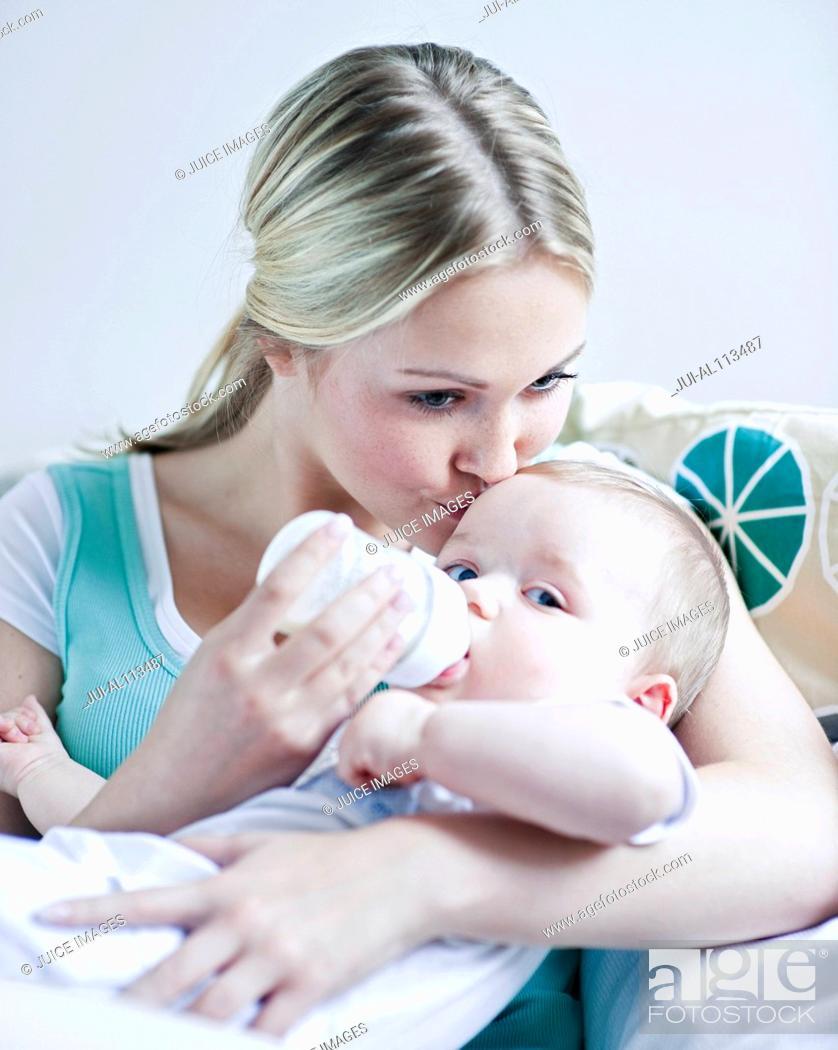 Stock Photo: Teenage girl feeding baby boy.