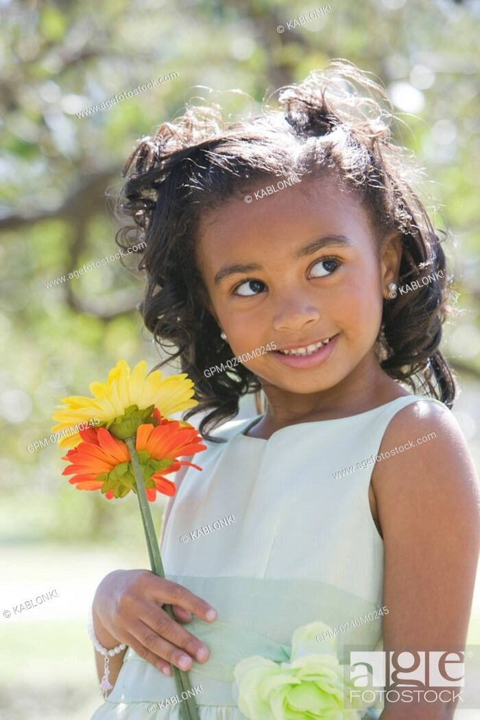 Imagen: Portrait of African American girl in dress standing in park holding flowers.