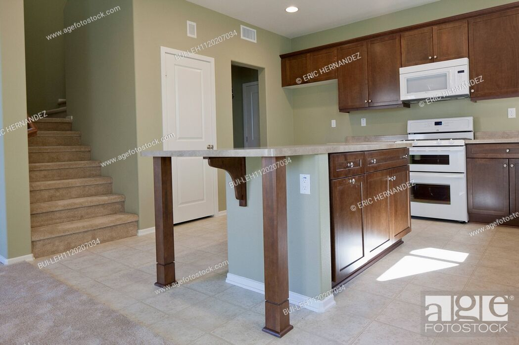 Imagen: Kitchen having brown cabinets and island at home.