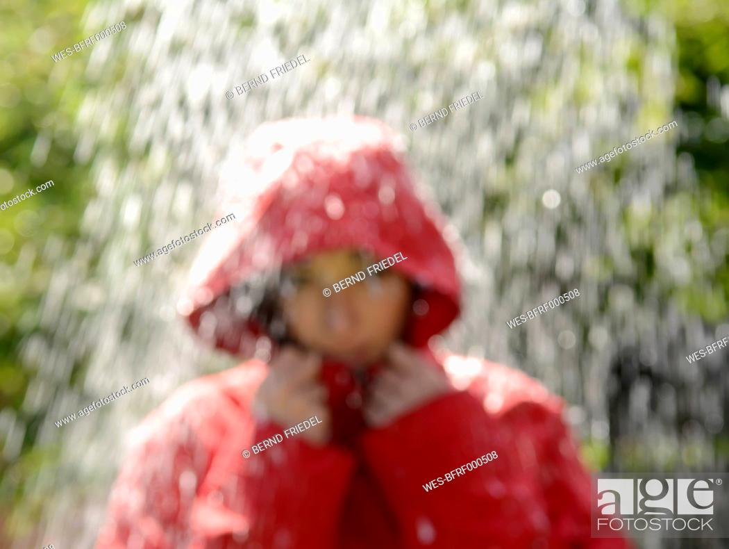 Stock Photo: Blurred portrait of young woman wearing red hooded jacket standing in the rain.