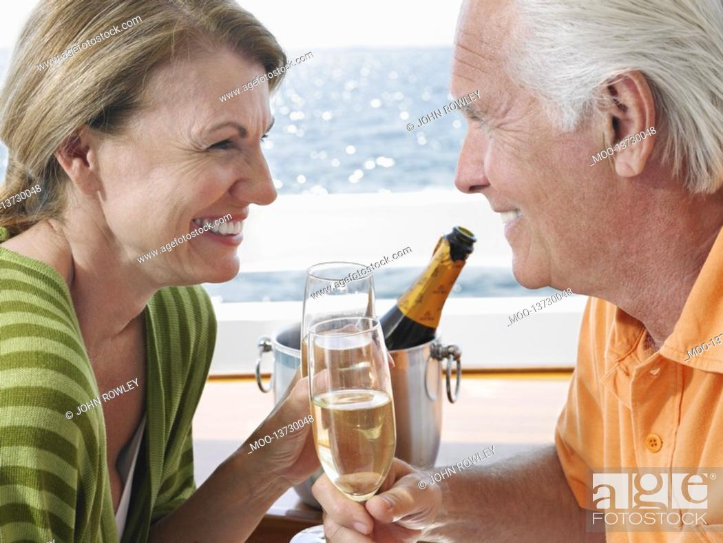 Stock Photo: Middle-aged couple drinking champagne on yacht side view close-up.