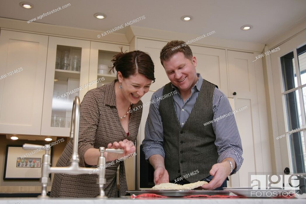 Stock Photo: A married couple cooking and cleaning up in the kitchen of their home.