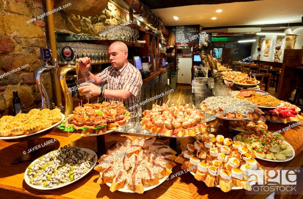Stock Photo: Waiter serving beer, Pintxos, Bar Taberna Aralar, Parte Vieja, Old Town, Donostia, San Sebastian, Gipuzkoa, Basque Country, Spain.