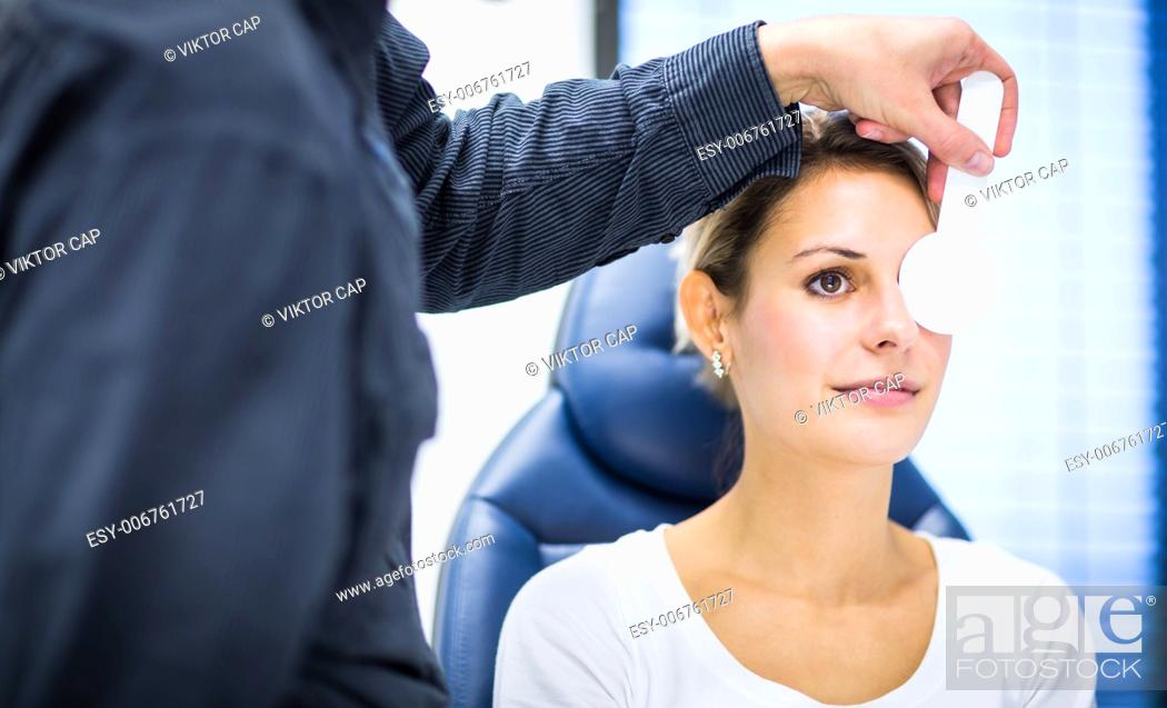 30cd23801a5 Stock Photo - Optometry concept - pretty young woman having her eyes  examined by an eye doctor optometrist (color toned image shallow DOF)