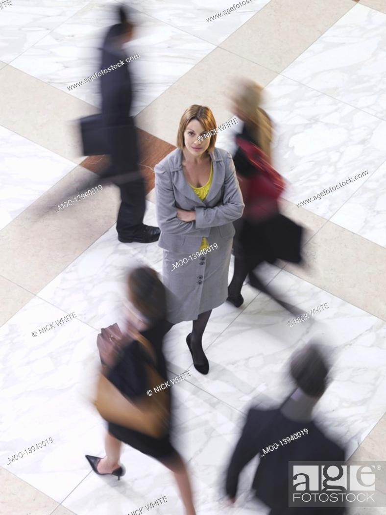 Stock Photo: Business woman standing amongst people walking elevated view long exposure.