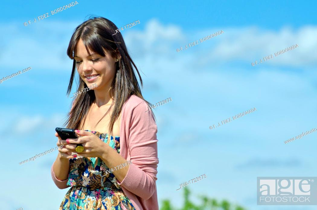 Stock Photo: Pretty girl with cell phone in outdoors.